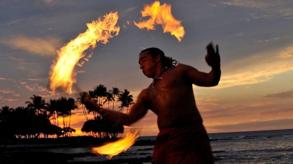 Show item 1 of 8. fire dancer in a luau in hawaii