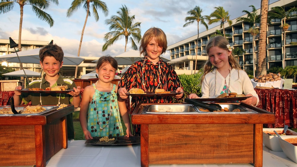Show item 4 of 8. Group of kids getting plate of food at a luau in Hawaii