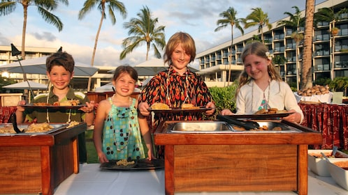 Group of kids getting plate of food at a luau in Hawaii