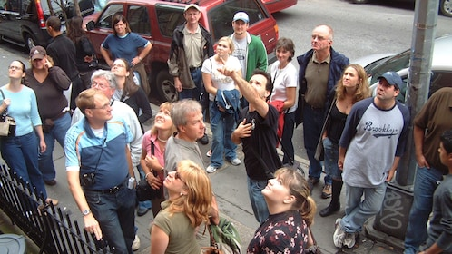 Tour guide pointing with talking to group on culture walk in Greenwich Village