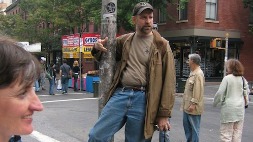 Tour guide holding onto light post, talking to group on culture walk in Greenwich Village