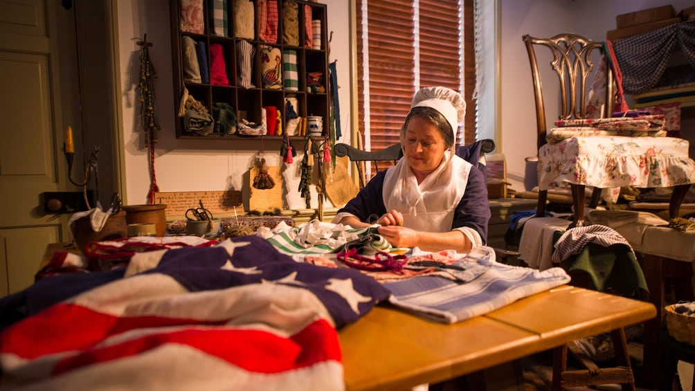 Charger l'élément 3 sur 5. Betsy Ross actress poses for photo while working on flag in home in Philadelphia