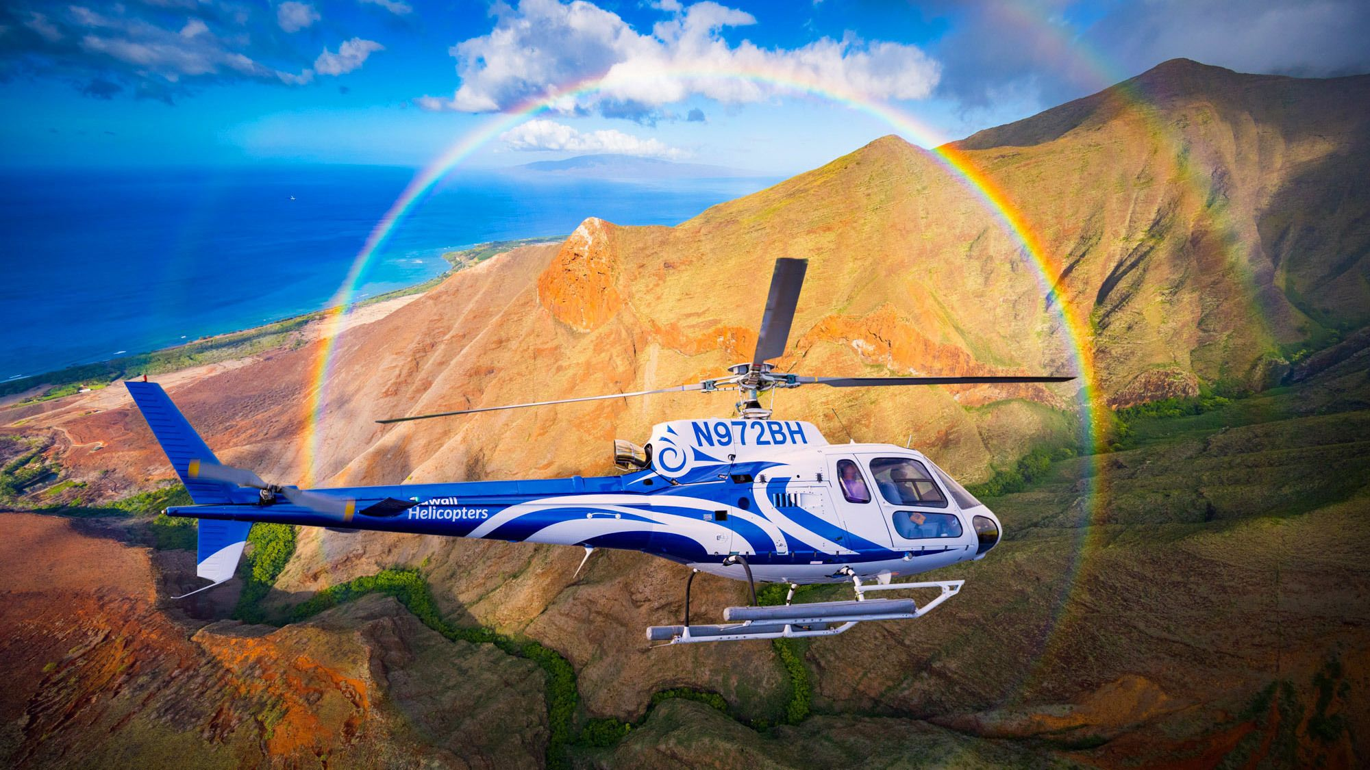 Helicopter flying over Maui with a rainbow