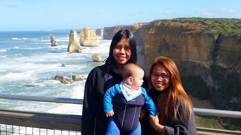 Women and baby pose in front of the 13 apostles in Australia