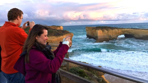 Tourists take pictures of London Bridge Rock formation