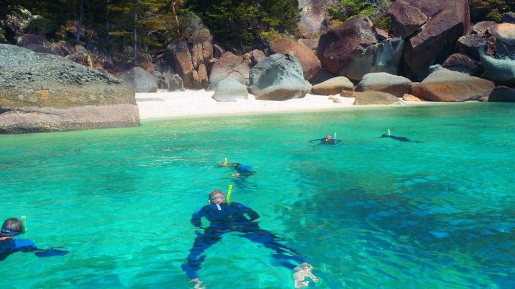 Show item 2 of 5. Snorkelers in a cove