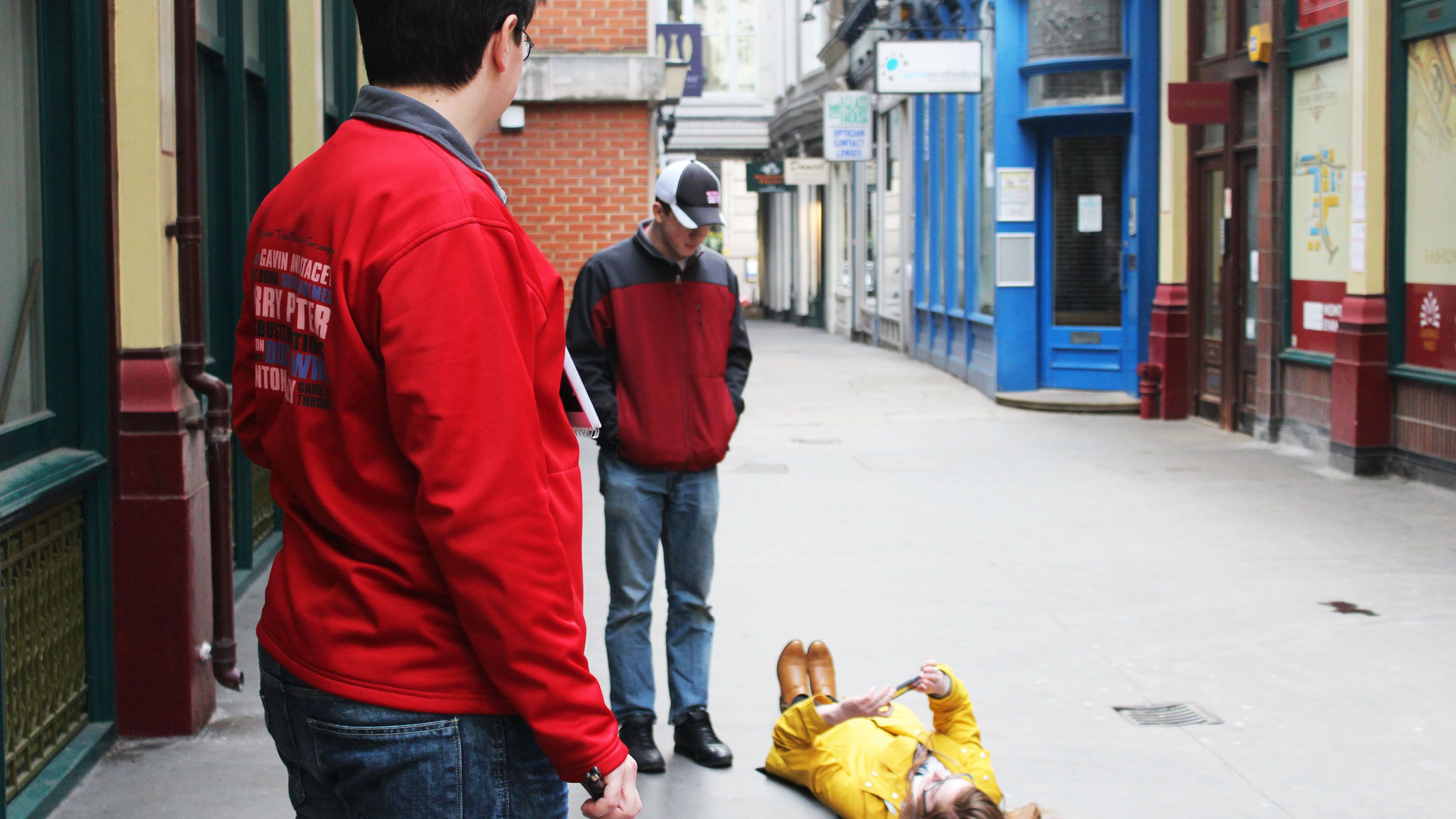 Tourist lying on ground, taking picture, while tour guide waits in London