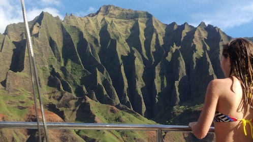 woman observing cliffs of kauai from boat