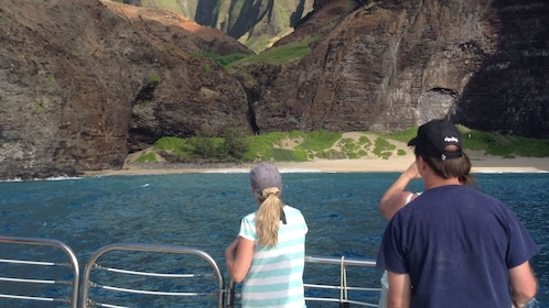 people looking at shore from boat in kauai