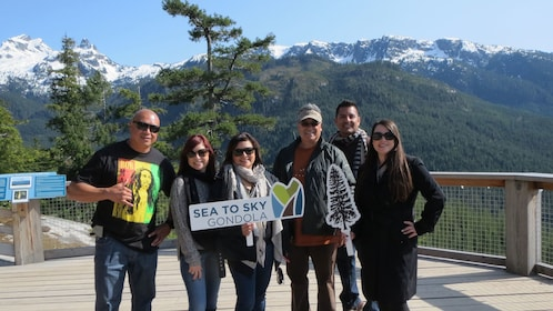 Group posing for photo with Sea To Sky Gondola sign in British Columbia