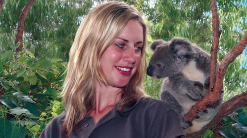 Woman smiling while looking at a koala in Australia