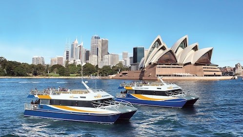 Two manly fast ferry boats in the water in front of the Sydney Opera House in Australia