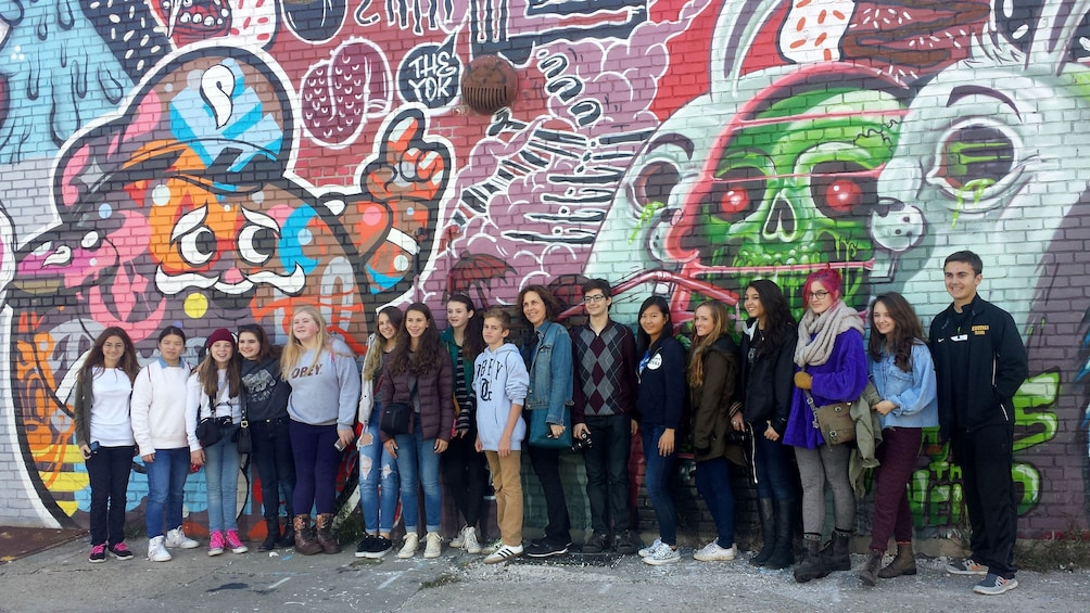 Show item 7 of 7. Tour group in front of graffiti wall mural in Brooklyn