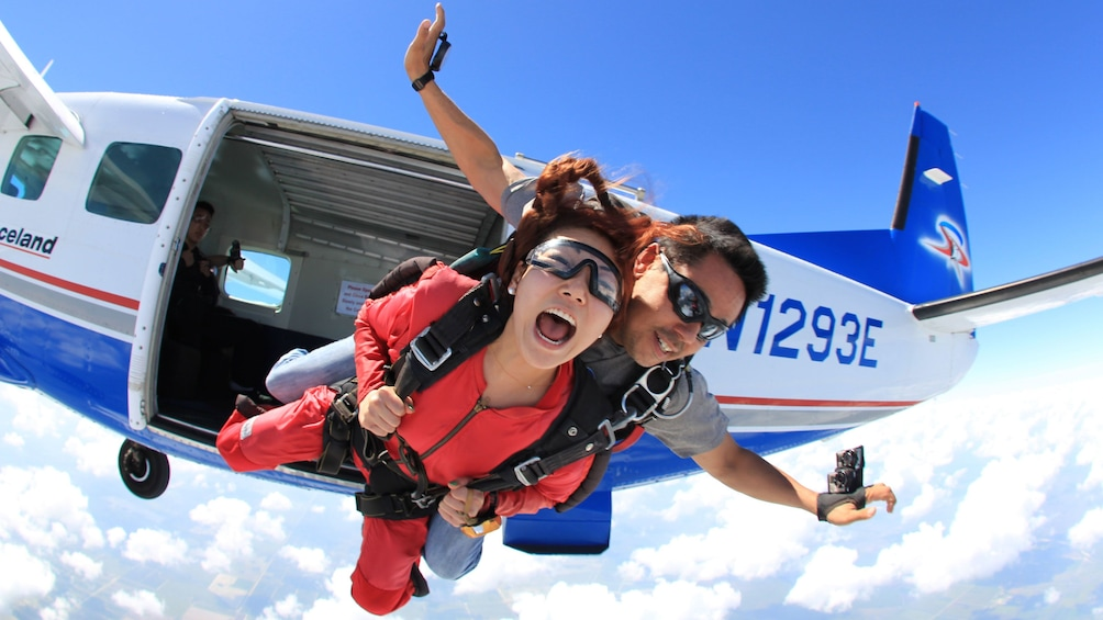 Show item 2 of 5. Woman skydiver with instructor jumping from plane over Atlanta