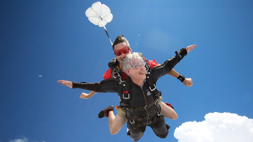 Show item 4 of 5. Woman skydiving with instructor over Atlanta