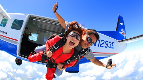 Tandem sky divers jump out of a plane
