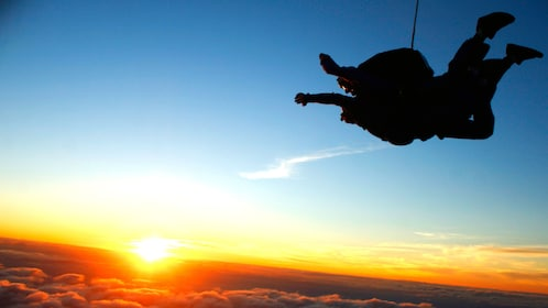 Tandem skydivers jump as the sun sets