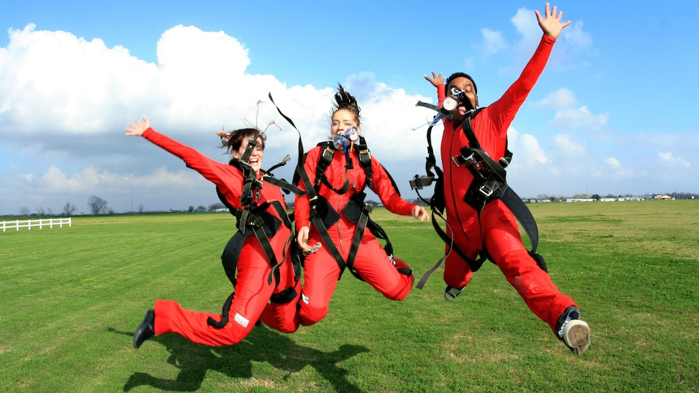 Show item 2 of 5. Three skydivers jump in excitement on the ground