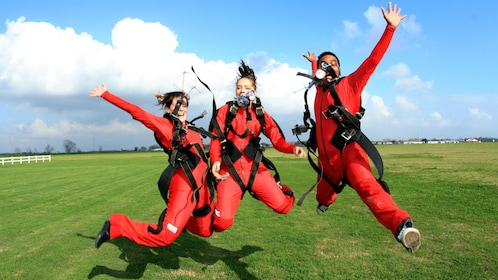 Three skydivers jump in excitement on the ground