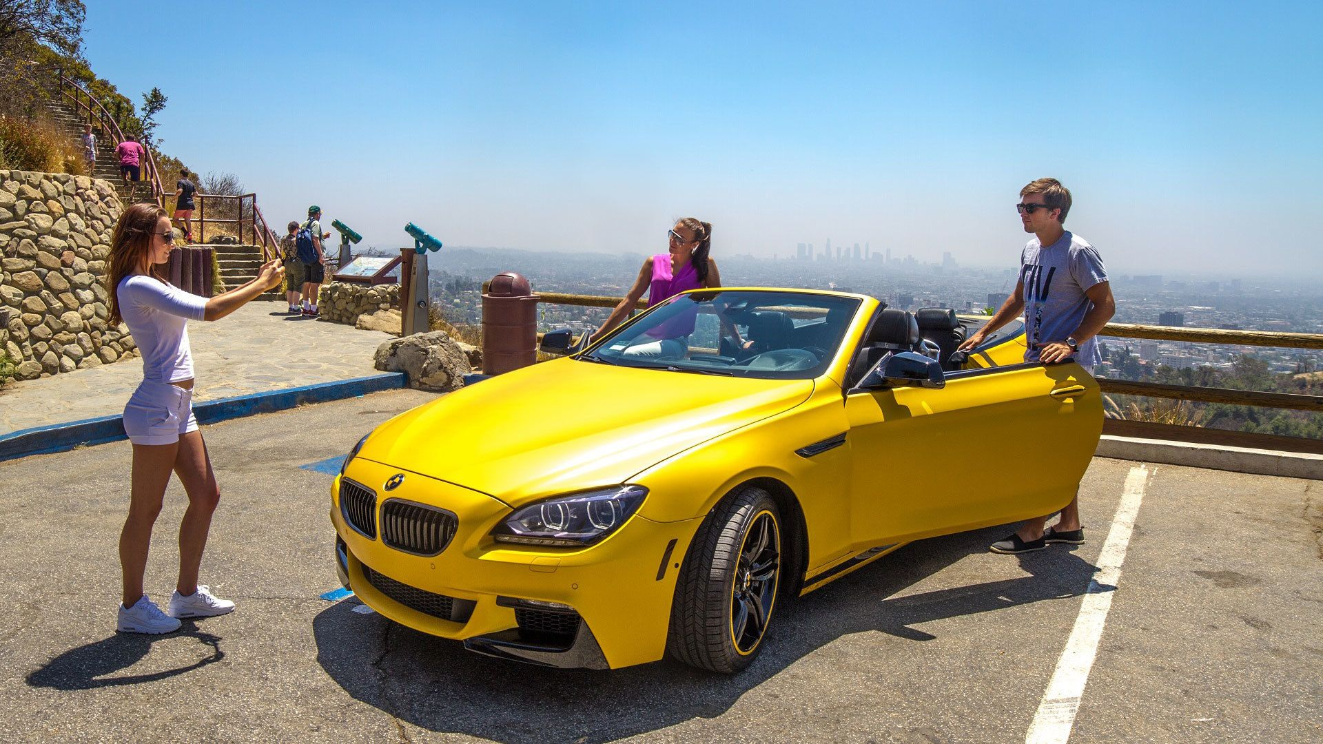 Couple posing with BMW sport convertible at overlook of Los Angeles