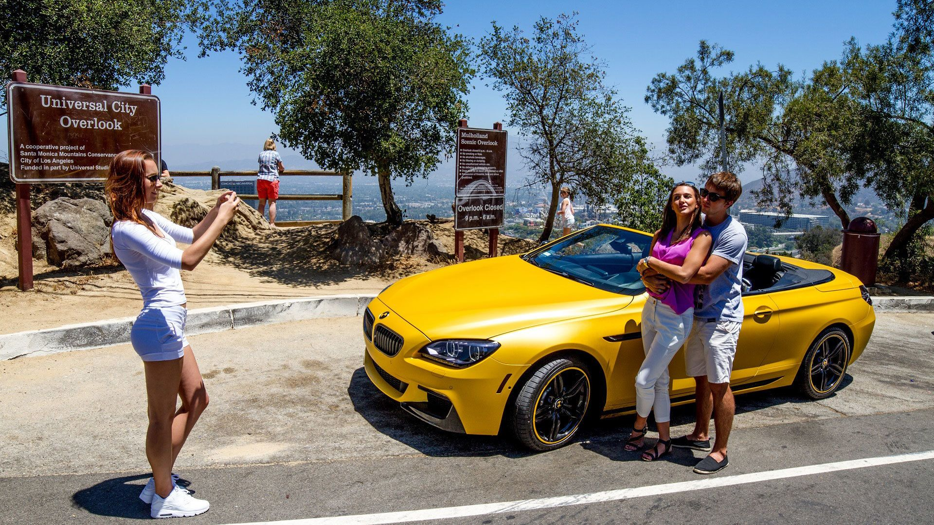 Couple posing for photo next to BMW sports convertible in Los Angeles