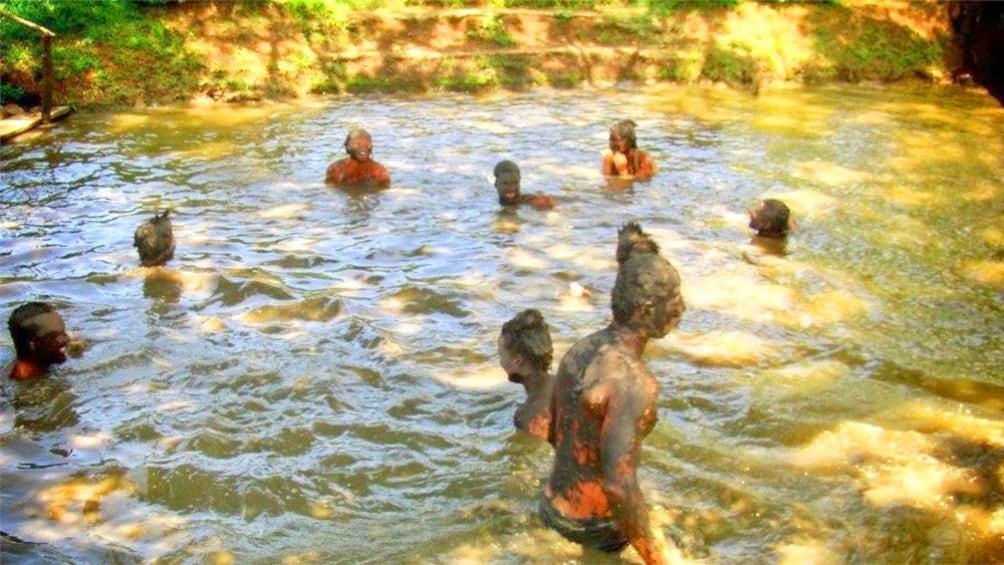 Show item 3 of 5. People in a mud pool in Fiji