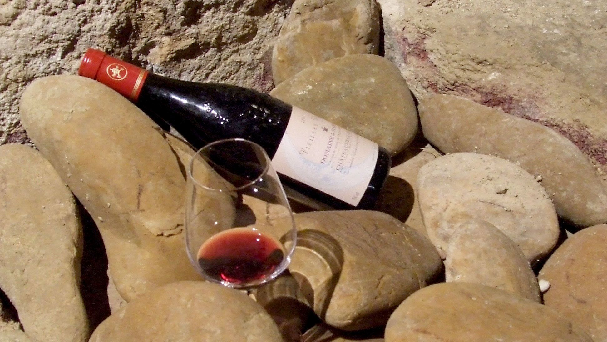 Bottle and glass of red wine on a rock in Rhone Valley