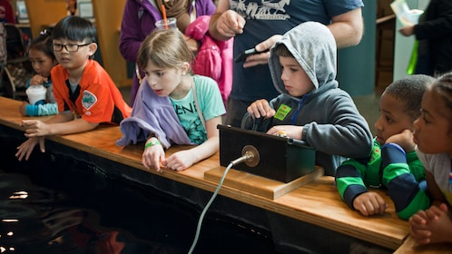 Children focusing on object in water table at Independence Seaport Museum