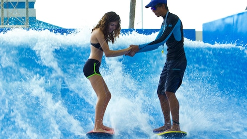 Woman holds hands with instructor as she rides the flowrider wave generator in Aquaworld Cancun