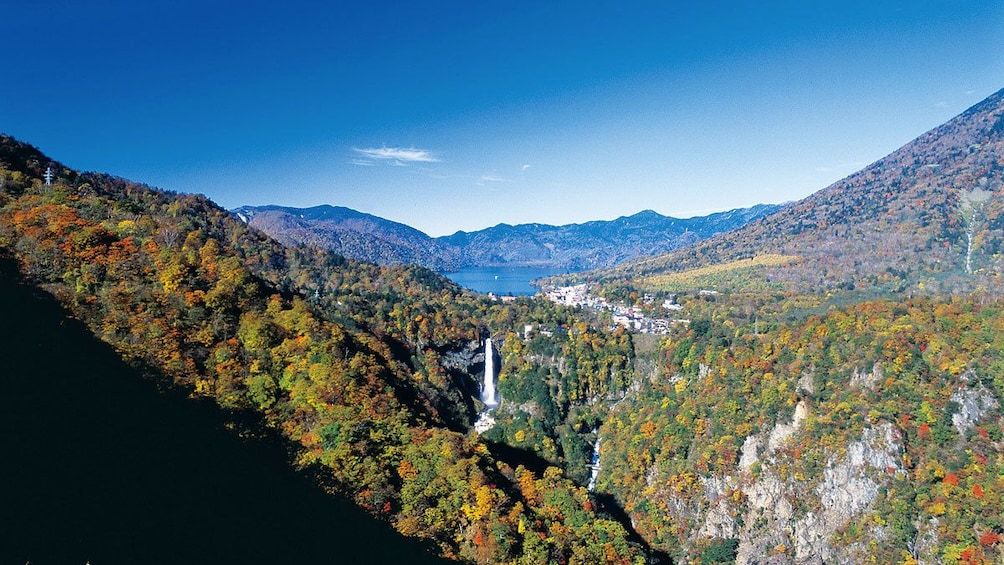 Ariel view of waterfall amongst cliffs and tree over mountains in Nikko