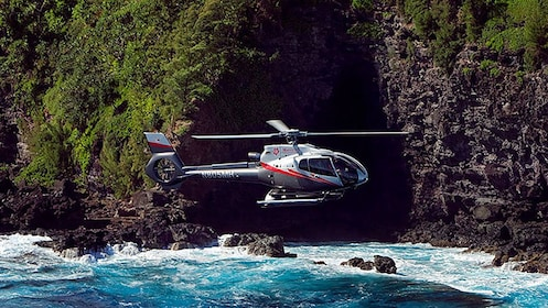 Helicopter flying near sea cave in Hana