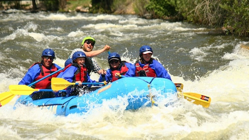 Rafters heading down Clear Creek rapids with guide in Denver
