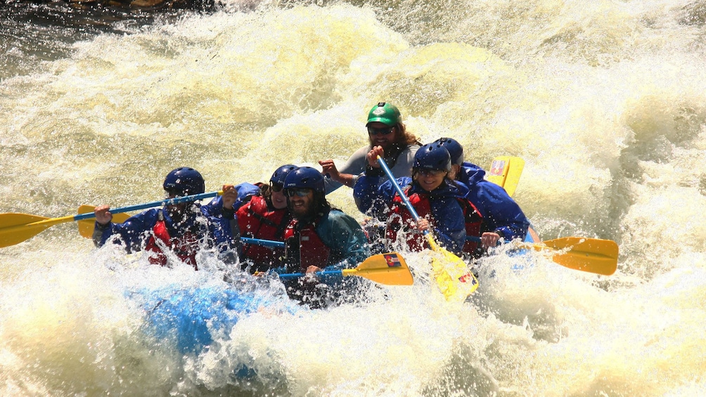 Show item 3 of 5. Rafters hitting rapids on Clear Creek with guide in Denver