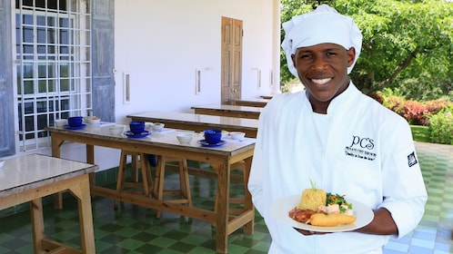 Chef holding a plate of food in Ocho Rios