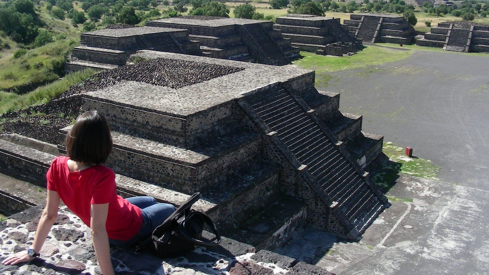 Show item 1 of 9. Woman sitting on top of ruins at Teotihuacan in Mexico