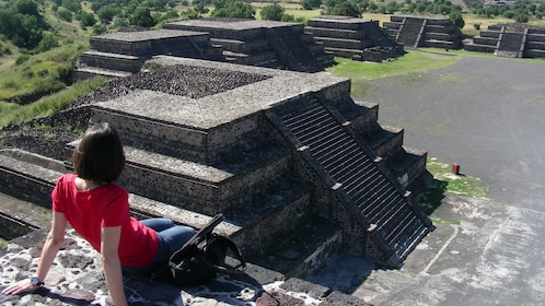 Woman sitting on top of ruins at Teotihuacan in Mexico