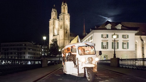 View of tuk tuk parked on street with cathedral in background in Zurich