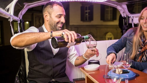 Man pours wine while group has fondue in back for tuk tuk in Zurich