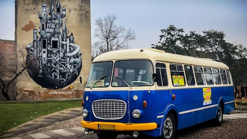 Tour bus in front of artwork on building wall in Praga district
