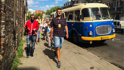 Tour guide leads group from bus in Praga district