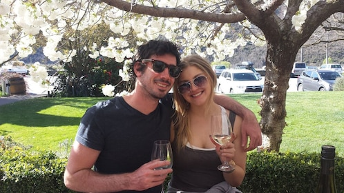 Couple with wine posing for picture at winery in Queenstown