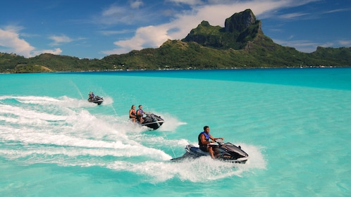 Group of people on three jet skis in tropical waters of Bora Bora