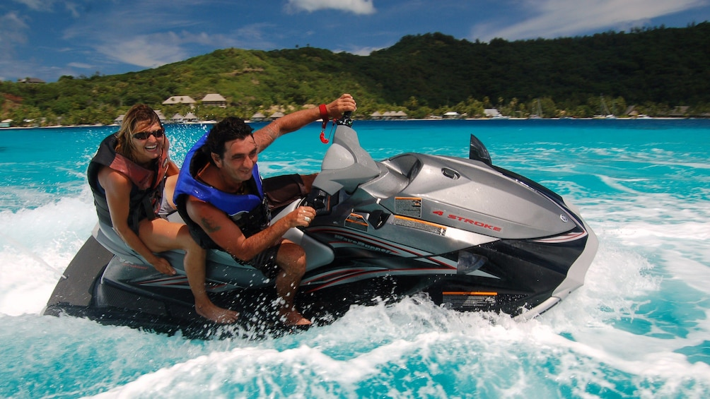 Show item 2 of 8. People banking turn on jet ski in tropical waters of Bora Bora