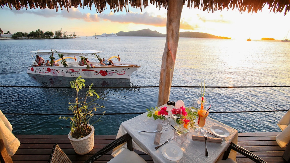 Show item 1 of 7. Dinner setting with sunset and cruise in background in Bora Bora