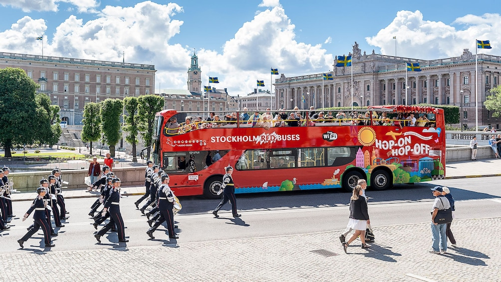 Foto 1 van 9. Red Buses Hop-On Hop-Off double decker bus stops on street as royal guard marches by in Stockholm