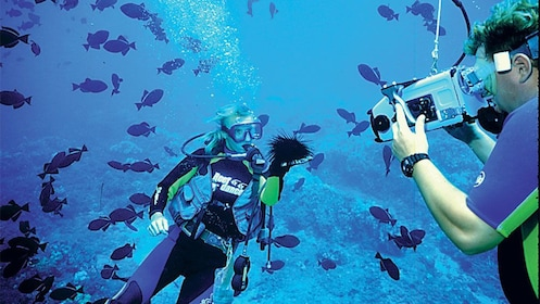 People filming under water while scuba diving in Maui
