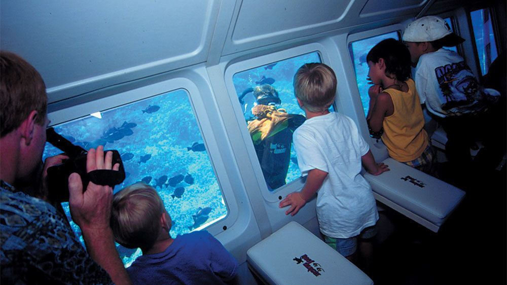 Kids looking out the window at scuba diver in the Glassbottom Reef explorer in Maui