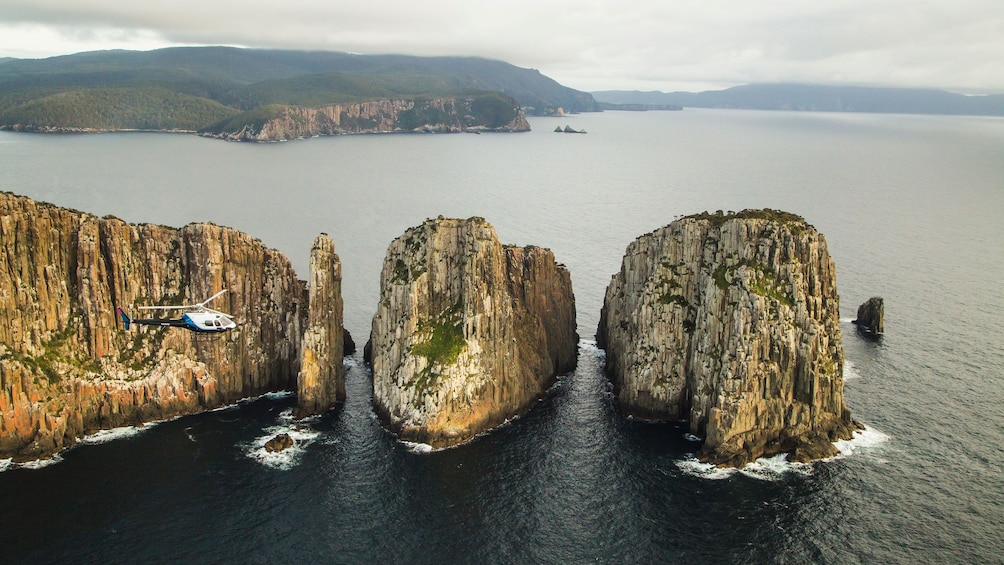 Show item 3 of 9. Helicopter flies near sea cliffs in Hobart