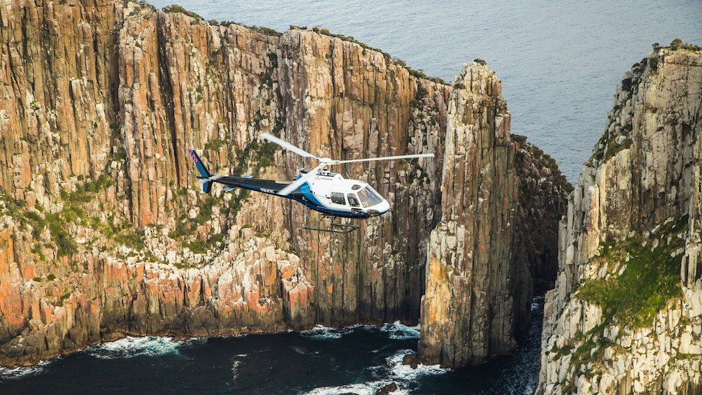 Show item 2 of 9. Close up of helicopter flying near sea cliffs in Hobart
