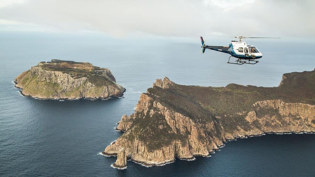 Show item 4 of 10. Helicopter flys near cliffs of Tasman Island